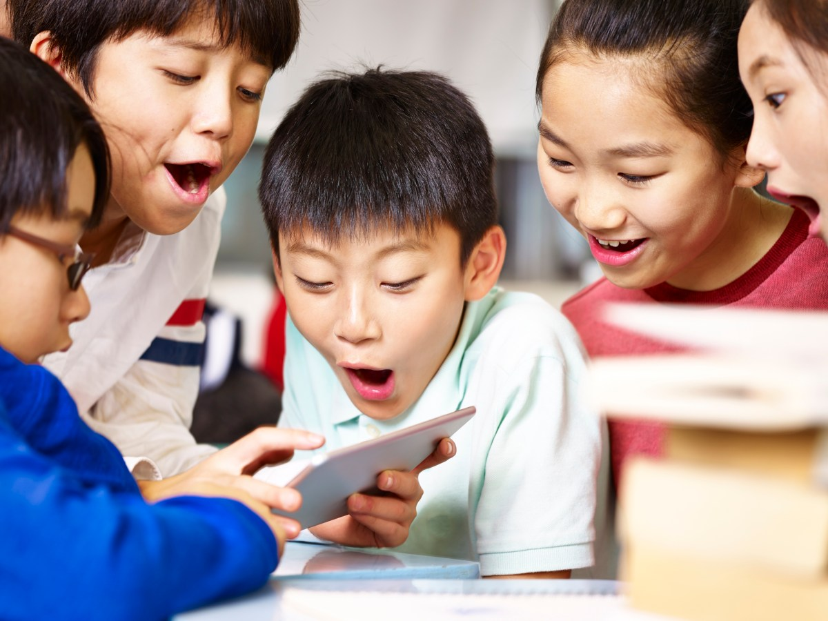 Asian school kids play games on a tablet. Usage of mobile phones for a range of purposes continues to rise in China. Photo: iStock