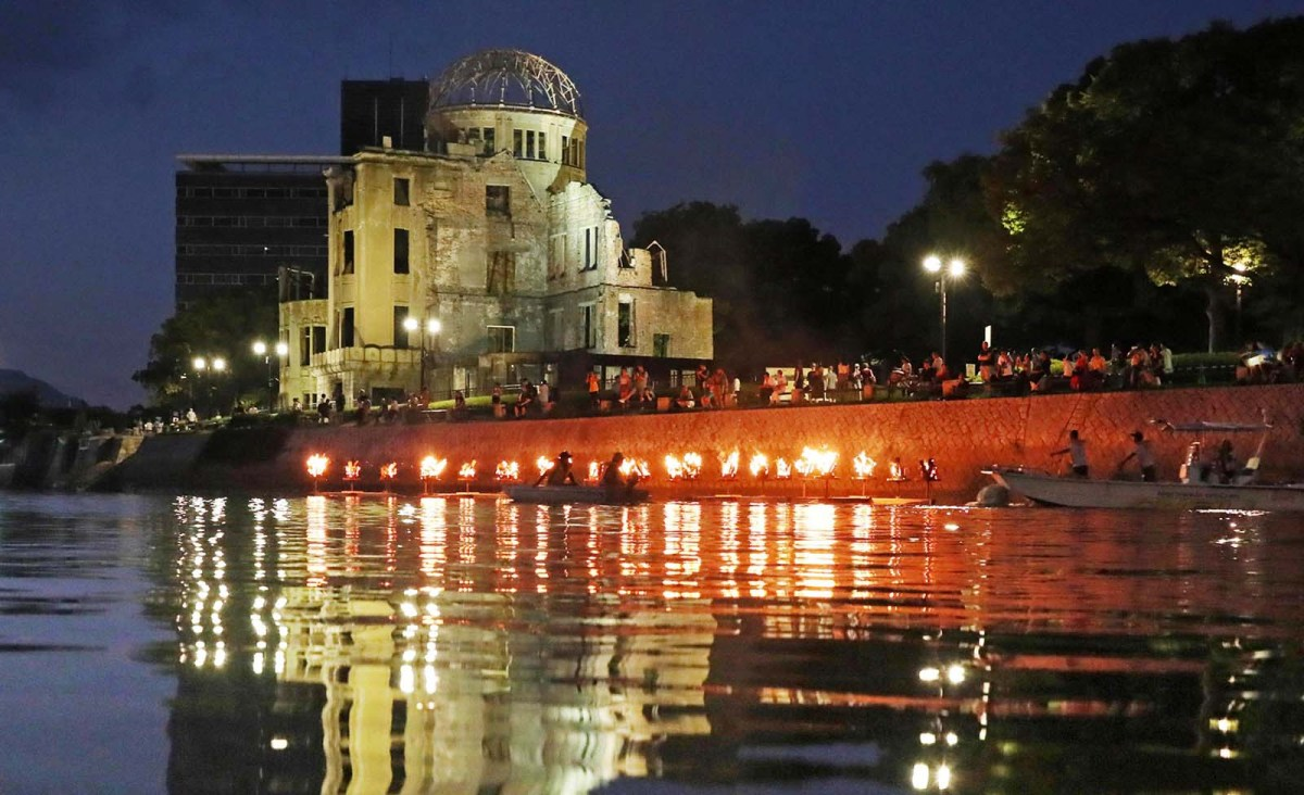 Boats carrying bonfires float along the Motoyasu-gawa River in front of the Atomic Bomb Dome in honor of the souls of those lost in the US atomic bombing of Hiroshima. The ceremony took place on Aug. 5, 2018, the eve of the 73rd anniversary of the bombing. Photo: The Yomiuri Shimbun