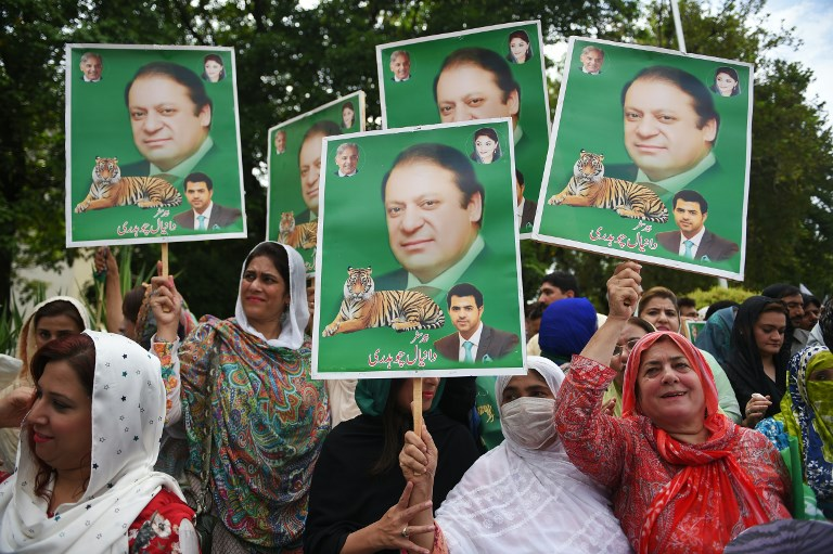 Supporters of Pakistani opposition parties carry placards with the picture of ousted Pakistani Prime Minister Nawaz Sharif outside the election commission office against the alleged election rigging in Islamabad on August 8, 2018.Pakistani opposition parties rejecting election results on August 2 have agreed to participate in the parliamentary process, take oaths and protest inside and outside the parliament. Imran Khan's party announced it has acquired enough seats in Pakistan's lower house through coalition talks to form a majority government. / AFP PHOTO / FAROOQ NAEEM