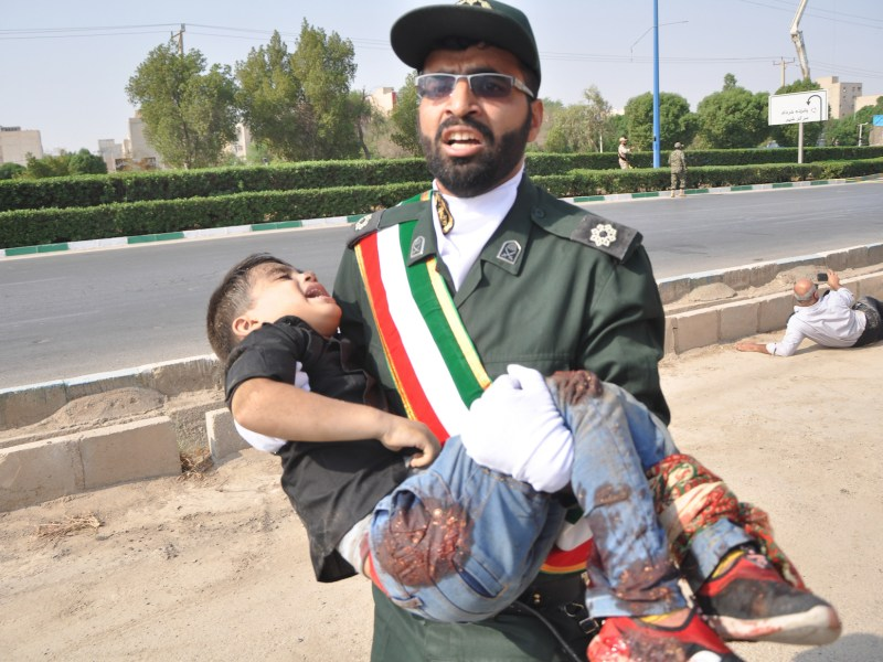 A member of Iran's Revolutionary Guards Corps carries an injured child at the scene of an attack on a military parade  on September 22, 2018 in the southwestern Iranian city of Ahvaz. Photo:   AFP / ISNA / Shayan Haji Najaf
