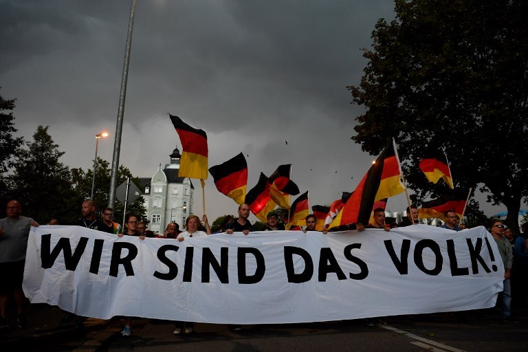 People hold a giant banner reading 'We are the people' during a march organized by the right-wing populist 'Pro Chemnitz' movement, on September 7, 2018, in Chemnitz, the flashpoint eastern city that saw protests marred by neo-Nazi violence. Photo: AFP  / John MacDougall