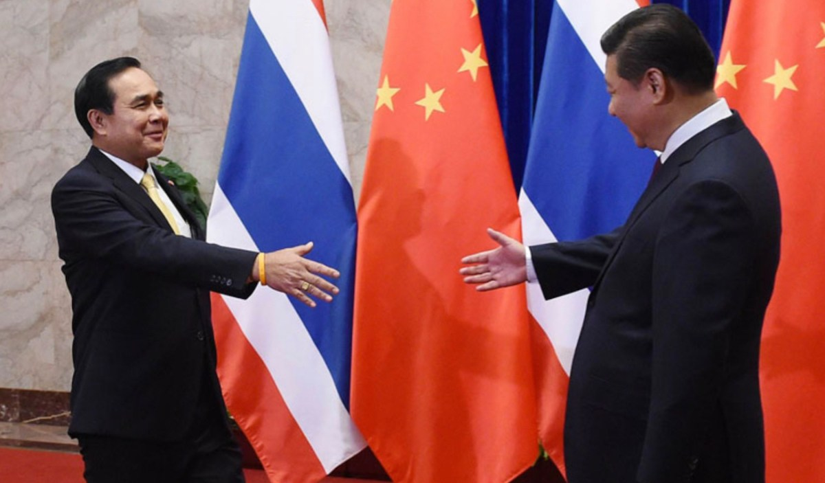 Thai Prime Minister Prayut Chan-ocha (L) and Chinese President Xi Jinping reach to shake hands in a file photo. Photo: AFP/Pool