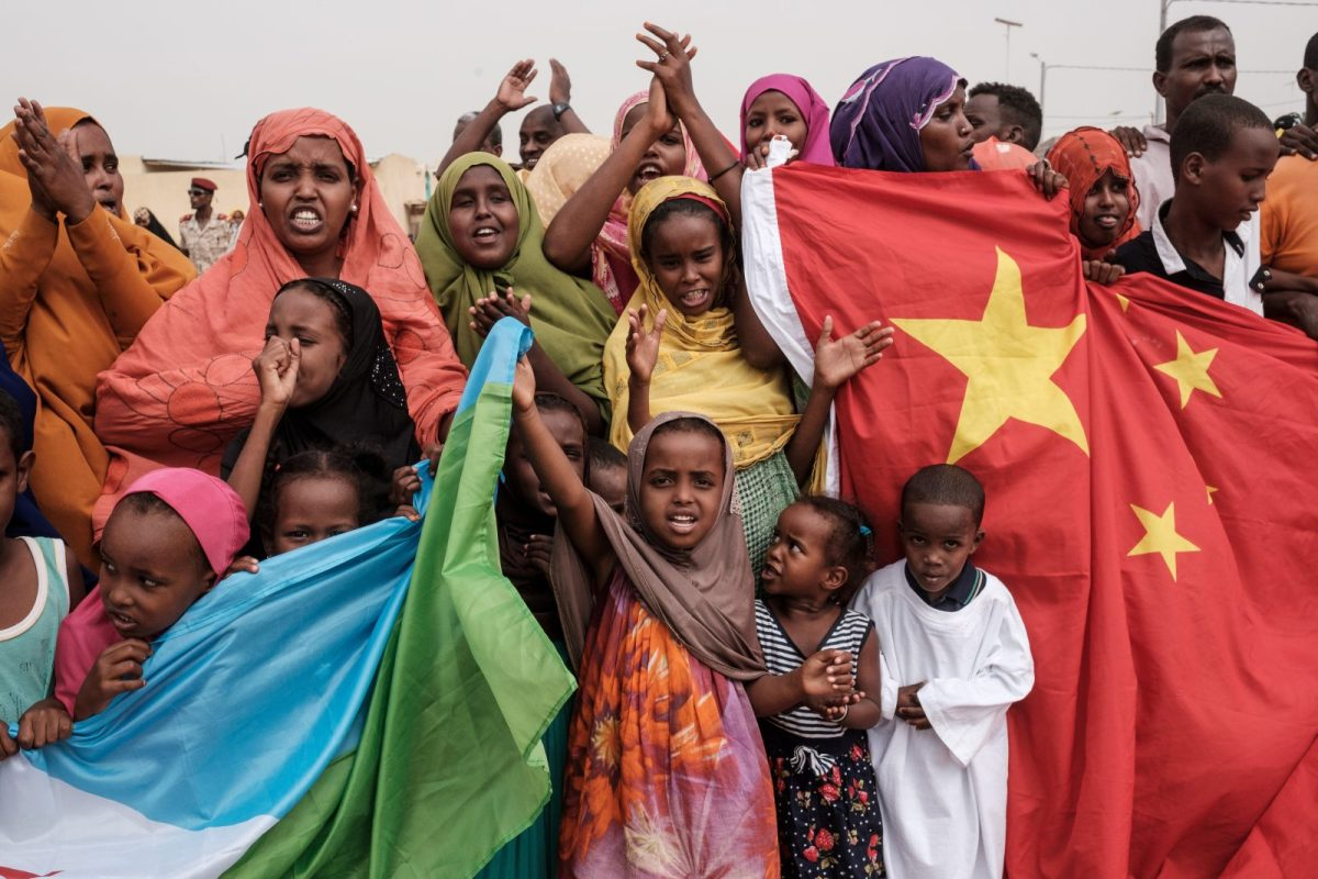 People hold Chinese and Djiboutian national flags as they wait for Djibouti's President before the opening of a 1,000-unit housing construction project in Djibouti on July 4, 2018. The project was financially supported by a Chinese company. Photo: AFP/Yasuyoshi Chiba