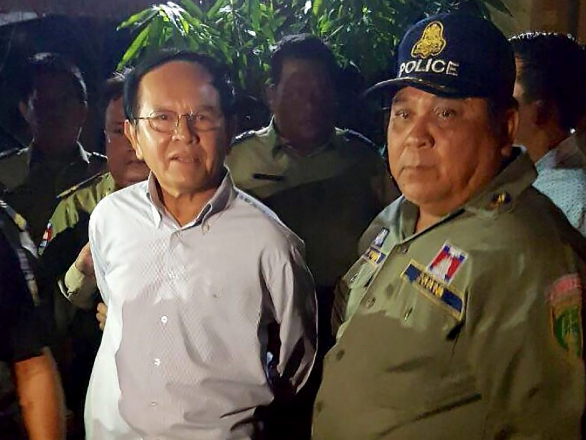 Cambodian opposition leader Kem Sokha (L) is escorted by police at his home in Phnom Penh.Sokha was released from jail early on September 10, 2018, a year after he was detained on treason charges, as the country's strongman ruler loosens his grip on opponents after sweeping one-sided elections. / AFP PHOTO / STR
