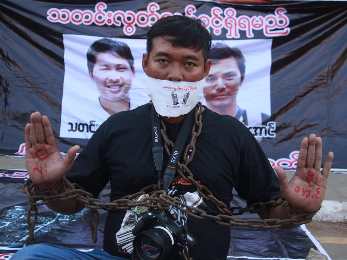 A journalist poses during a protest by local media to demand the release of Reuters journalists Wa Lone and Kyaw Soe Oo (pictured in posters behind). Photo: AFP/Thiha Lwin