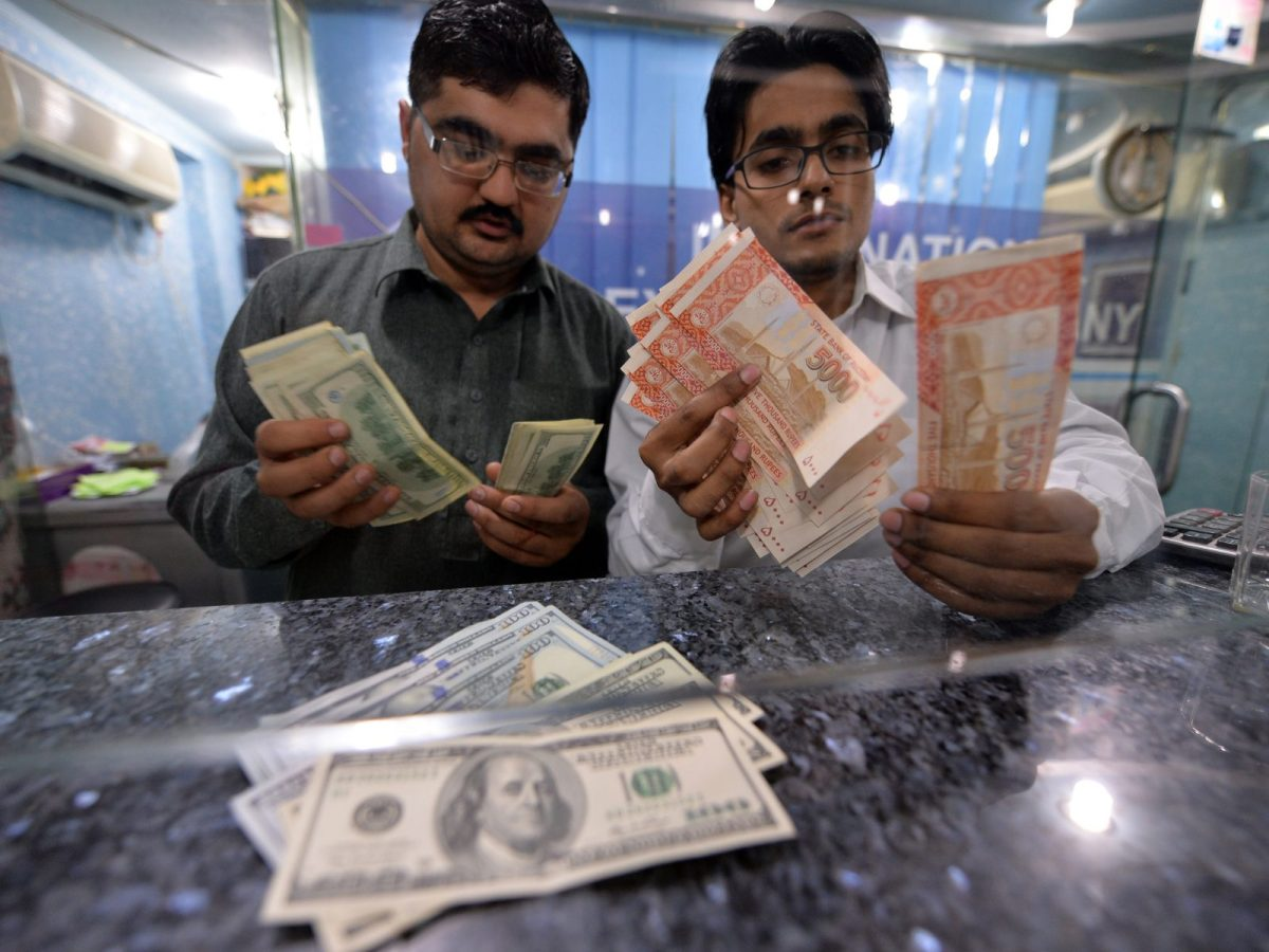 Money dealers count Pakistani rupees and US dollars at an exchange in Islamabad. Photo: AFP/ Aamir Qureshi