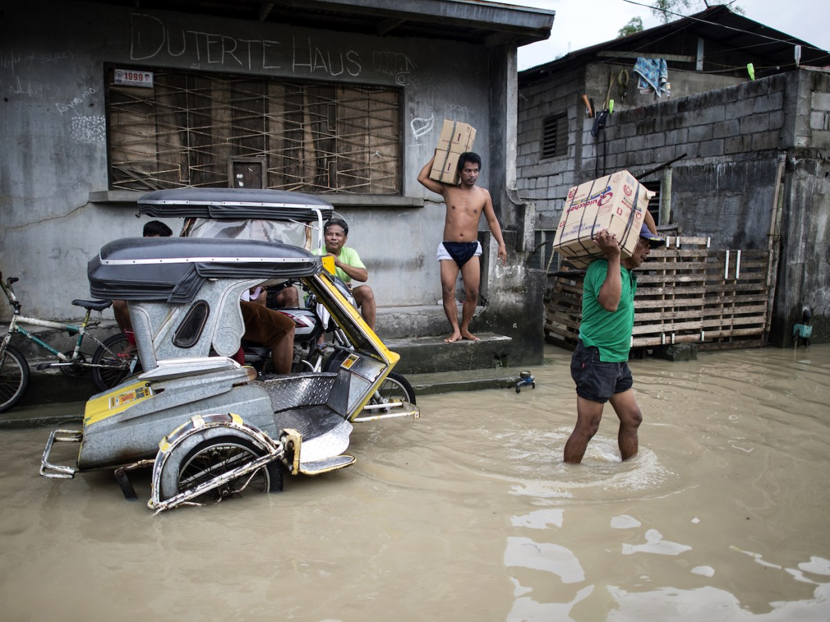 Residents wade through a flooded street in the aftermath of Super Typhoon Mangkhut in Calumpit, Bulacan, Philippines on September 17, 2018. Photo: AFP/Noel Celis