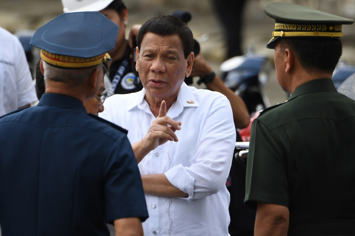 Philippine President Rodrigo Duterte (C) talks to military chief General Carlito Galvez (R) and national police chief Oscar Albayalde during a ceremony where seized vehicles and motorcycles were destroyed at the customs yard in Manila on May 30, 2018. Photo: AFP/Ted Aljibe