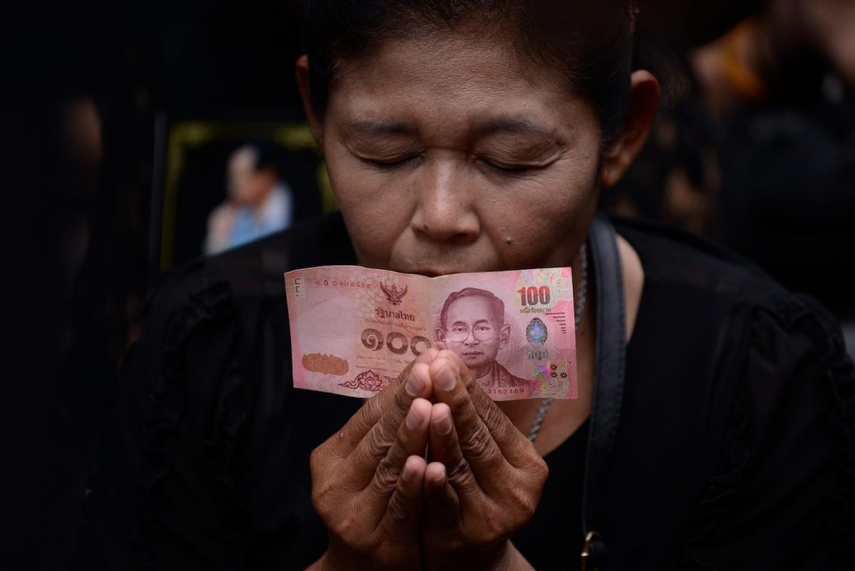 A mournful Thai holds a Thai baht note. Photo: NurPhoto via AFP Forum/Anusak Laowilas