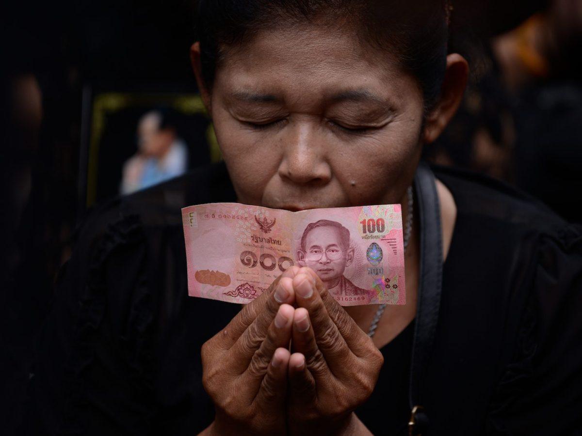 A mournful Thai holds a Thai baht note. Photo: NurPhoto via AFP Forum/Anusak Laowilas
