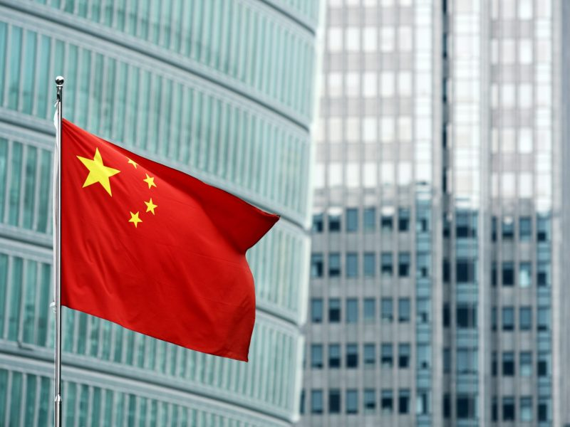 Chinese flag against modern buildings Photo: iStock