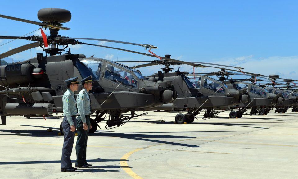 2018年7月17日,在桃園軍事基地舉行的啟用儀式上,兩名台灣軍人站在美國製造的AH-64「阿帕契」直升機前。相片:AFP / Sam Yeh
