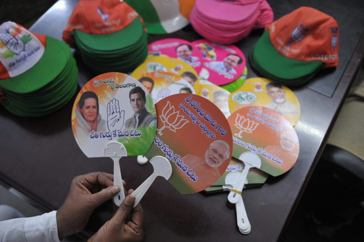A man holds election campaign material of the BJP and the Indian National Congress party ahead of the upcoming assembly elections in 2018. Photo: AFP / Noah Seelam