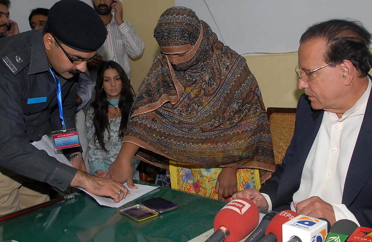 تظهر في هذه الصورة المأخوذة في ٢٠١٠ السيدة الباكستانية المسيحية آسيا بيبي (وسط) وهي تطبع بصمتها على ورق استئناف حكم الإعدام ضدها بتهمة الازدراء. الصورة: ا ف ب