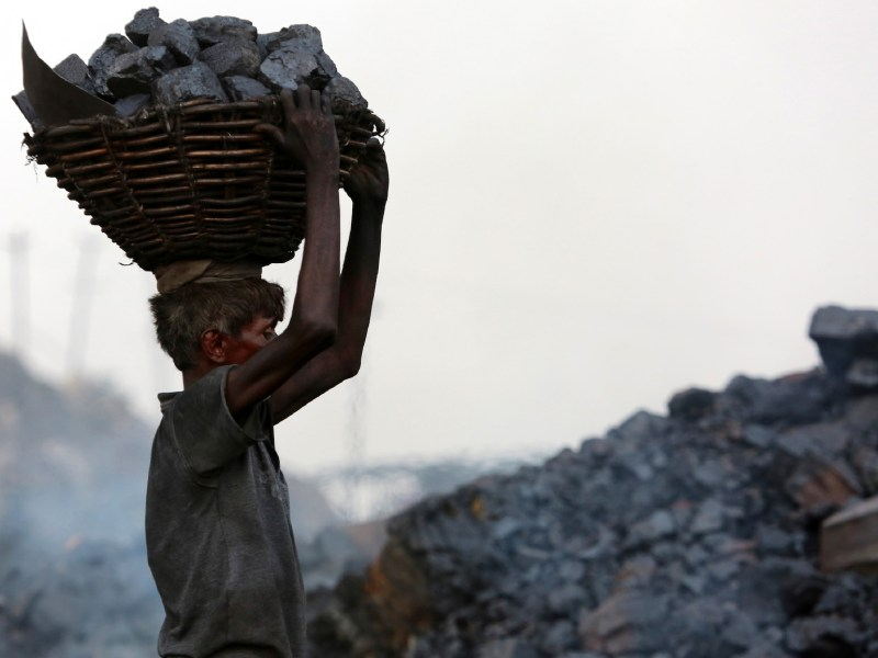 An Indian coal mine worker carries a basket of coal collected at a mine in the district of Dhanbad in the state of Jharkhand in June 2017. Photo: AFP/Sanjib Dutta