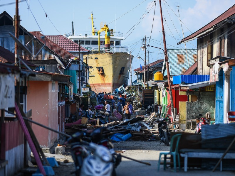Survivors walk past debris and a washed up passenger ferry in the Wani area of Sulawesi on Wednsday. More than 1,400 people were now known to have died in the quake-tsunami that smashed into the area. Photo: AFP/Jewel Samad