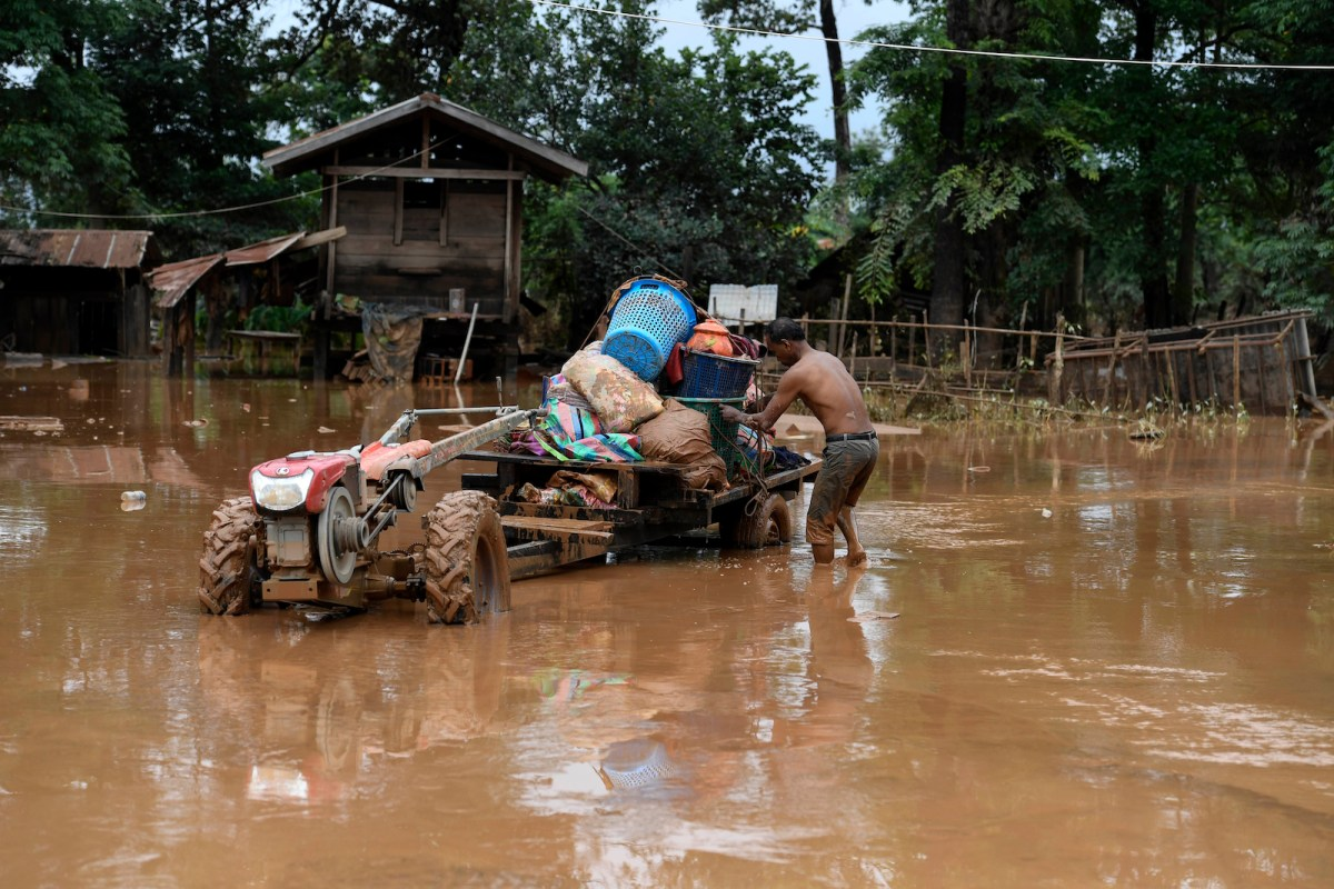 A man loads belongings on a tractor near his flooded home in Sanamxai in Attapeu province on July 26, 2018. Scores of people were missing after the dam collapse in southern Laos unleashed a torrent of water, washing away whole villages. Photo: AFP / Nhac Nguyen