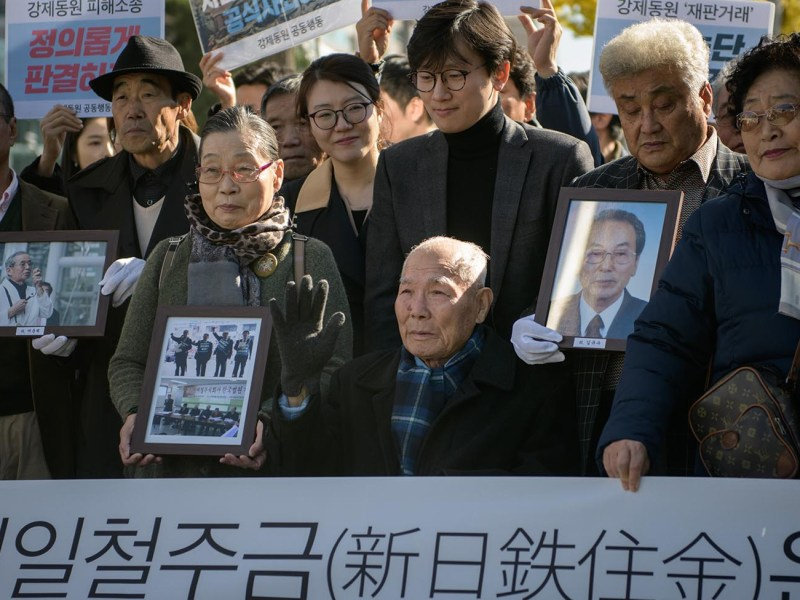 Lee Choon-shik (C), a victim of forced labor by Japan during its colonial rule of the Korean peninsula from 1910 to 1945, is surrounded by supporters and relatives outside the supreme court in Seoul on October 30, 2018. Photo: AFP/Ed Jones
