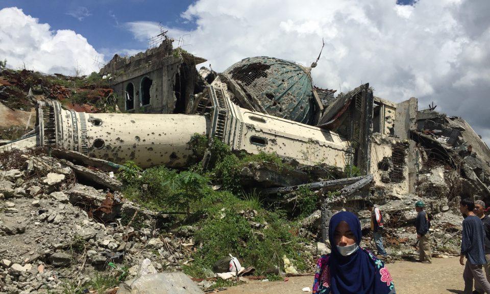 2017年5月23日,一名婦女在菲律賓南部馬拉維市嚴重受損地區或主要戰區的一座倒塌的清真寺前走過。相片:AFP Forum / Girlie Linao