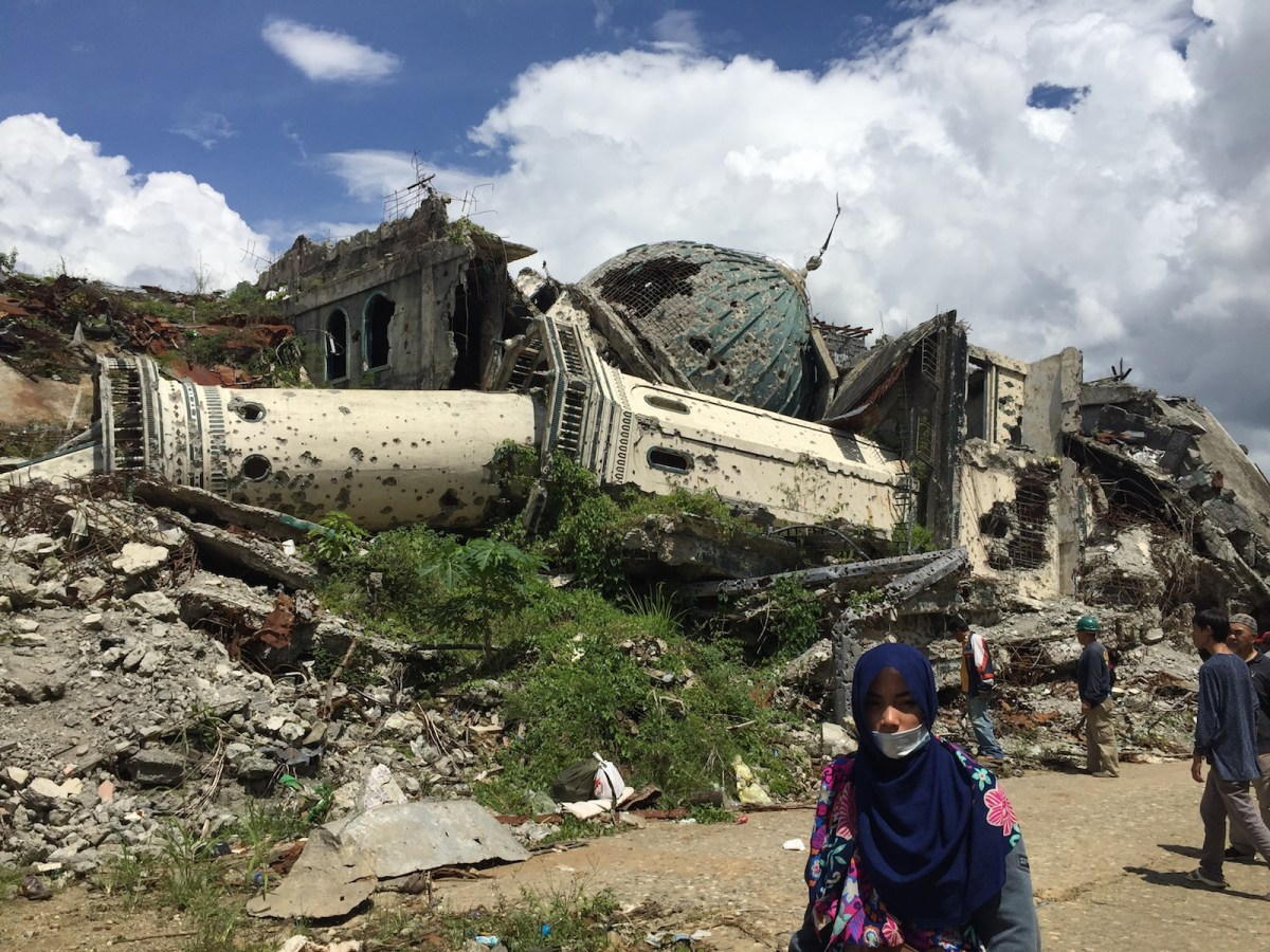 A woman walks in front of a toppled mosque at ground zero, or the main battle area, in Marawi City in the southern Philippines on May 23, 2017. Photo: Photo: AFP Forum/Girlie Linao