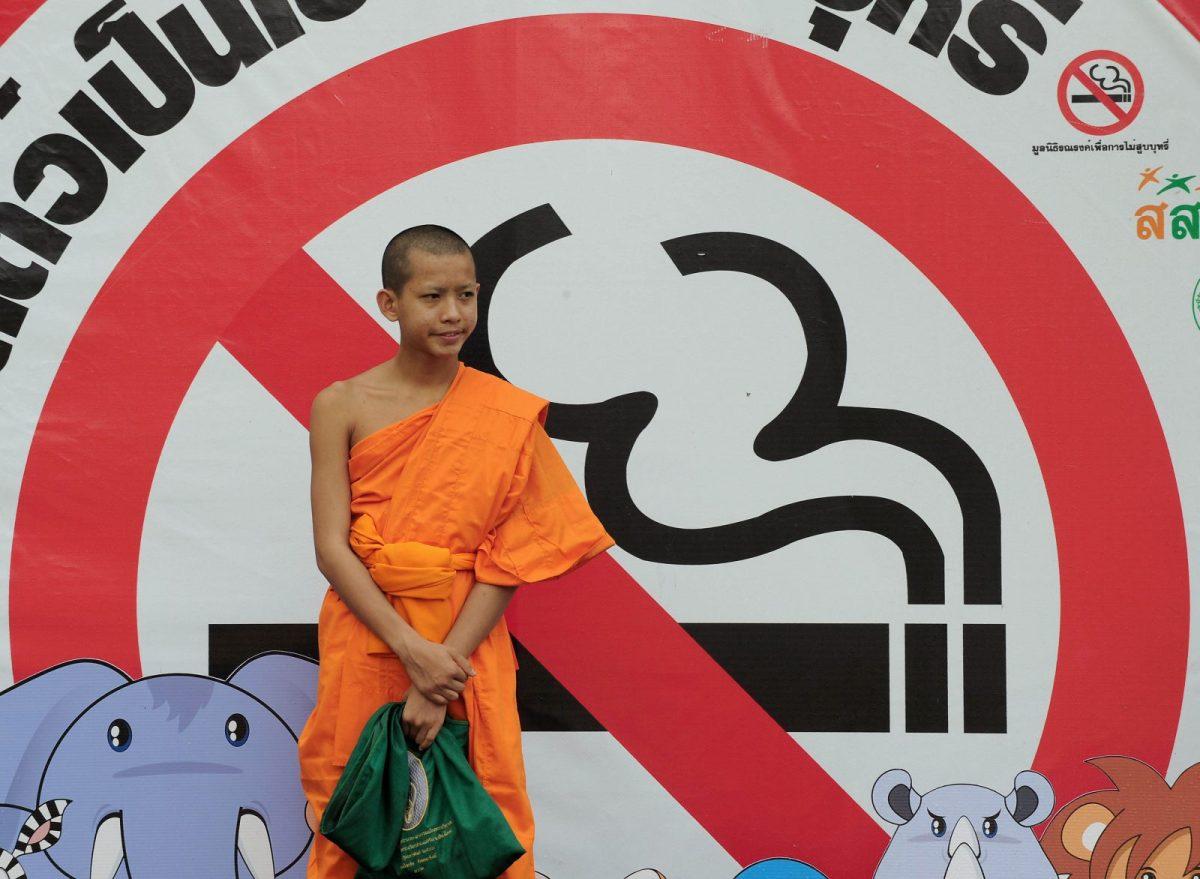 A Thai Buddhist monk in front of an anti-smoking billboard displayed at a Zoo in Bangkok. Photo: AFP/Pornchai Kitiwongsak