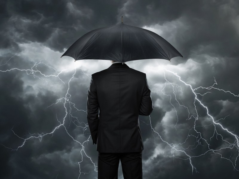 Businessman with umbrella standing in front of stormy clouds. Image: iStock