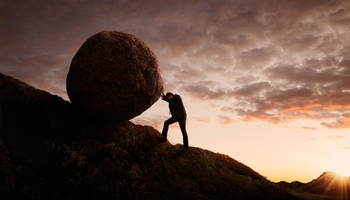 Silhouette of young businessman pushing large stone uphill with copy space. Image: iStock