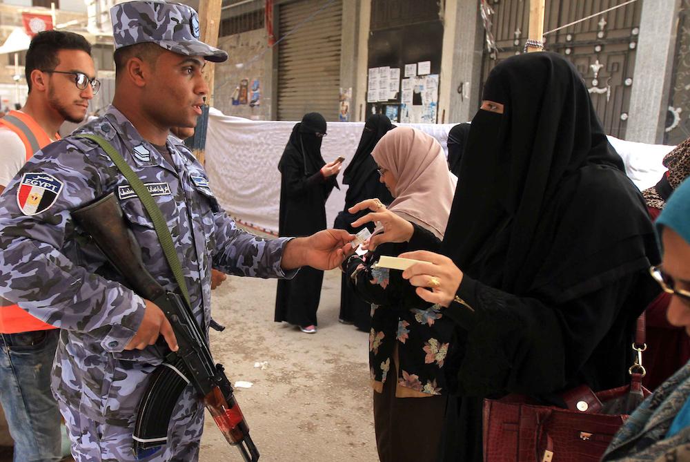 مصرية منتقبة تظهر بطاقتها لعسكري قبل دخول لجنة تصويت في منطقة المنتزه في الإسكندرية في أول أيام الانتخابات الرئاسية في 2018. صورة stringer / AFP