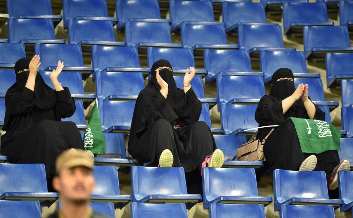 سعوديات يرتدين العباءة السوداء أثناء تشجيع السعودية في مباراة ودية مع العراق في إستاد جامعة الملك سعود في الرياض في ١٥ أكتوبر ٢٠١٨.  صورة: Fayez Nureldine / AFP