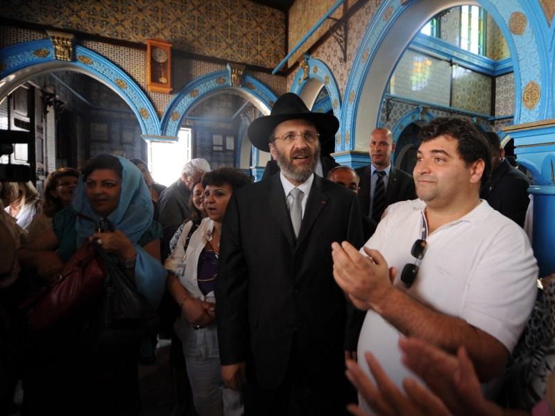 المرشد السياحي (يمين) رينيه الطرابلسي يقف بجانب الحاخام الأكبر في فرنسا جيل برنهايم (وسط) في زيارة لمعبد غريبة في جربة. تم اختيار الطرابلسي، وهو ينتمي للأقلية اليهودية بتونس، لوزارة السياحة في التغيير الحكومي الأخير في 5 نوفمبر/ تشرين الثاني 2018.  Photo: Fethi Belaid / AFP