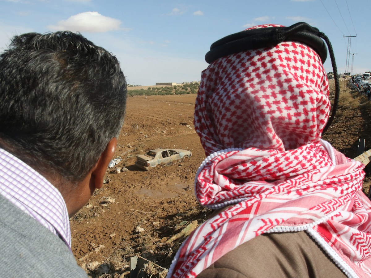 أردنيون يراقبون سيارة غارقة في الوحل بعد السيول، في مدينة مبادة بالقرب من العاصمة عمان في ١٠ نوفمبر/تشرين الثاني ٢٠١٨. صورة: KHALIL MAZRAAWI/AFP