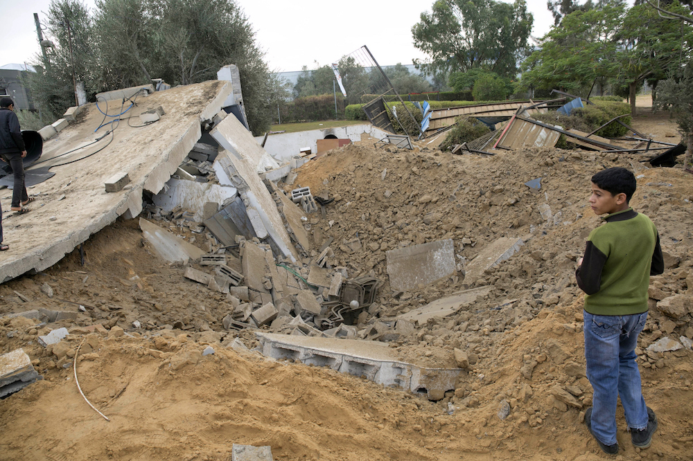 فلسطينيون عند بقايا مبنى مدمر بعد الضربات الجوية الإسرائيلية في خان يونس بقطاع غزة في ١٢ نوفمبر/تشرين الثاني ٢٠١٨. صورة: SAID KHATIB/AFP