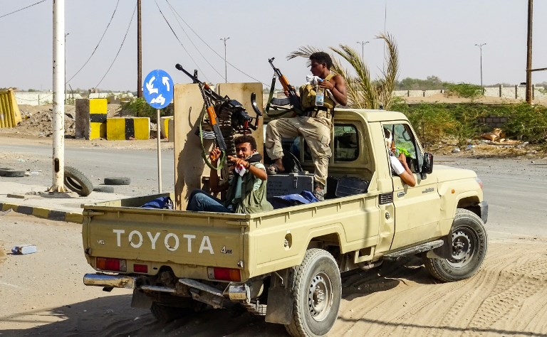 Yemeni pro-government forces cheer as they ride in the back of a pickup truck mounted with a machine gun in an industrial district in the eastern outskirts of the port city of Hodeida on November 18. Photo: AFP