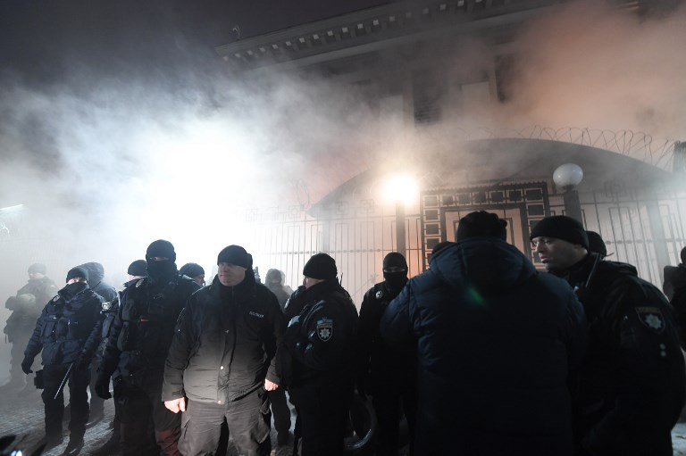 Policemen stand in front of the Russian Embassy in Kiev late on Sunday, while smoke from a flare thrown by protesters is seen during a rally, following an incident in the Black Sea off Moscow-annexed Crimea, in which three Ukrainian naval vessels were seized by a Russian border guard vessel. Photo: AFP