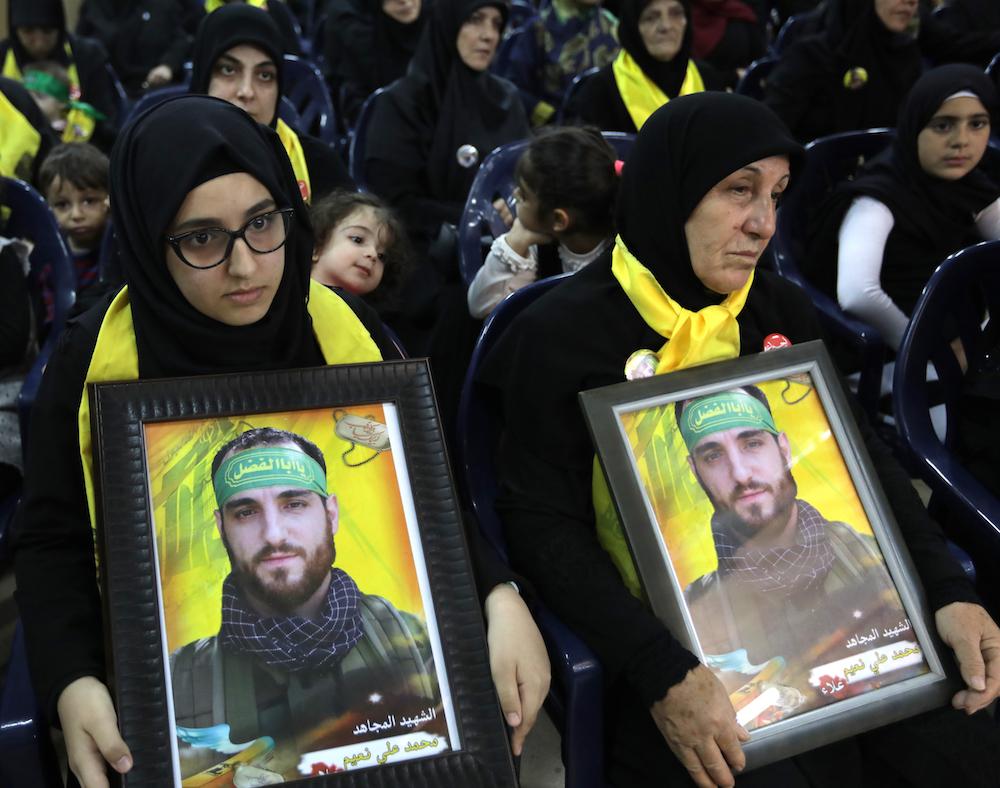 أقارب محاربي حرب الله الذين قتلوا في معارك في سوريا يحملون صورهم في تجمع قي ضاحية بجنوب بيروت في ١٠ نوفمبر/تشرين الثاني ٢٠١٧. صورة: Anwar Amro /AFP