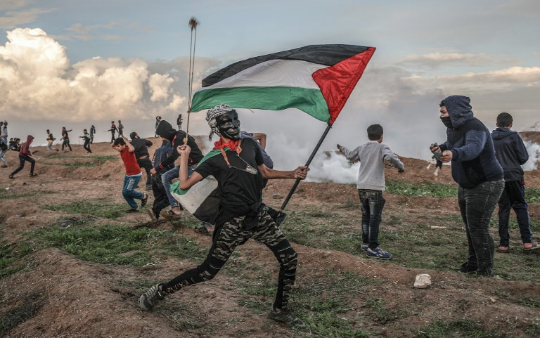 "A Palestinian demonstrator throws a stone during a ""Great March of Return"" demonstration near the Israel-Gaza border on November 23. Photo: Ali Jadallah / Anadolu Agency"