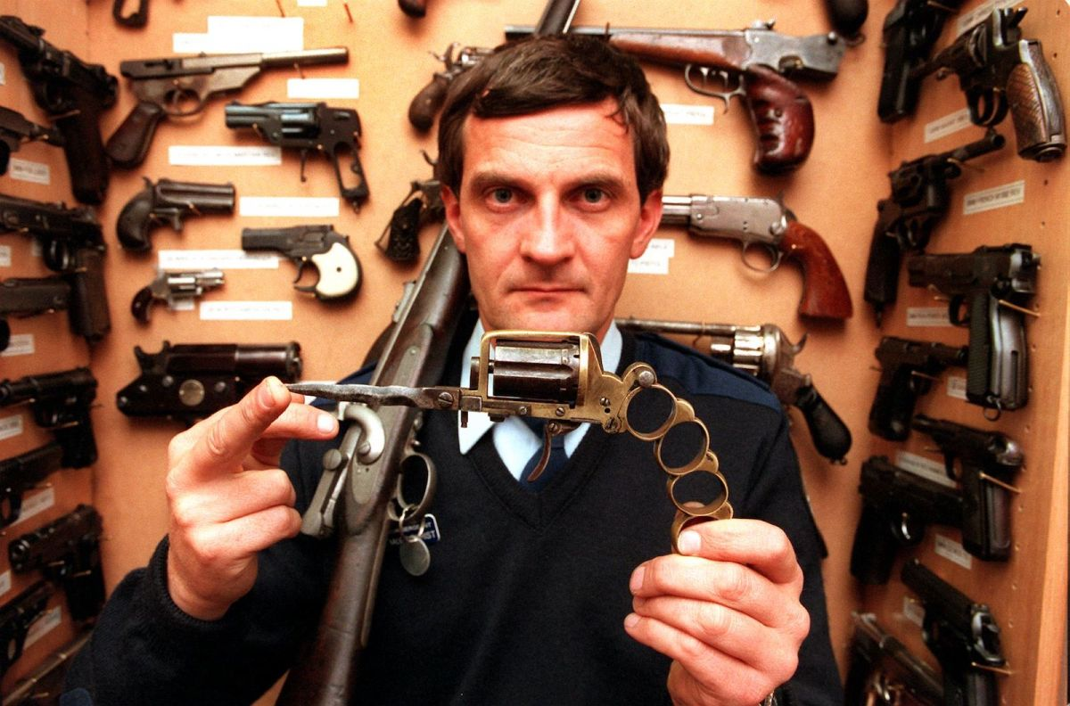An Australian police official displays a combination knife, pistol and knuckle duster from the New South Wales police armory in Sydney in a file photo: Photo: AFP/William West