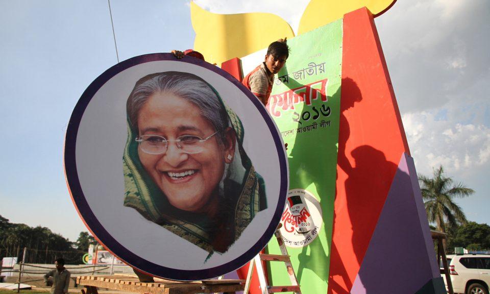 工人們在孟加拉首都達卡人民聯盟黨的國會大廈前張貼孟加拉總理哈西娜的肖像。相片:NurPhoto via AFP / Rehman Asad
