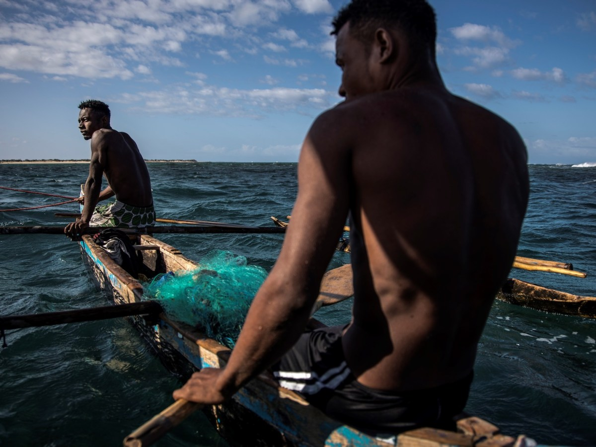 Malagasy fishermen sit in their boat in front of the fishing community of Anakao on November 4, 2018. Already threatened by global warming, these fishermen now have to struggle against Chinese fishing vessels amid news of a highly controversial deal with Chinese investors and Madagascar parastatal entities. Photo: AFP / Marco Longari