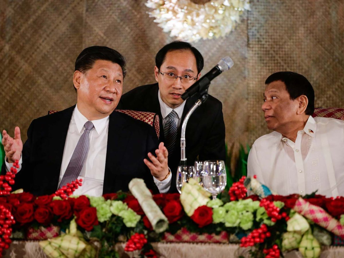 """Chinese President Xi Jinping (L) gestures as Philippines' President Rodrigo Duterte (R) looks on during a state banquet at the Malacanang Presidential Palace in Manila on November 20, 2018. Photo"""" AFP/Mark R. Cristino/Pool"""