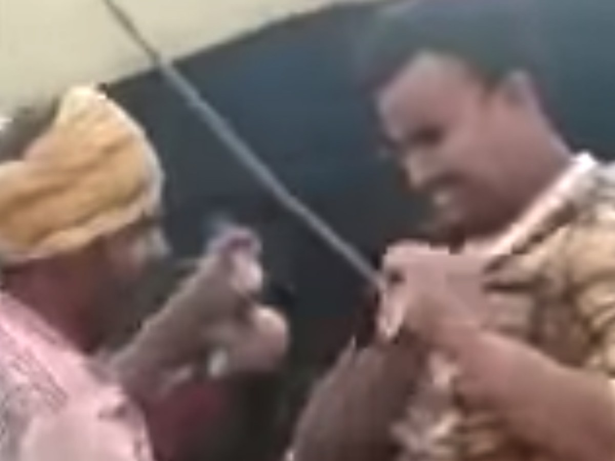 The snake charmer puts the cobra around the victim's neck. Photo: Screen grab from Youtube.