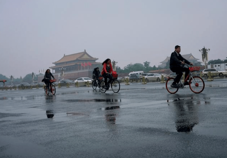 Cyclists in Beijing's Tiananmen Square on a rainy day. Photo: Xinhua