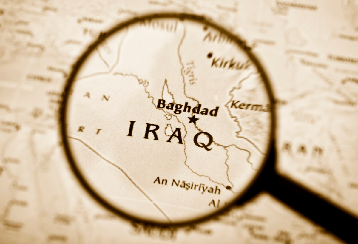 High resolution photograph of a magnifying glass over Iraq in a map.