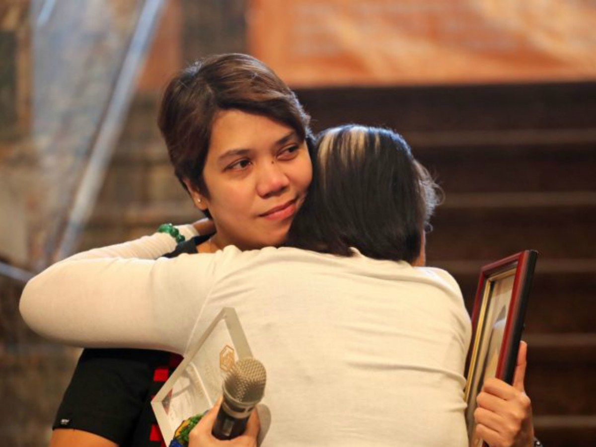 Filipina Melinda M Babaran hugs her mother after being presented with her award. Photo: CNA