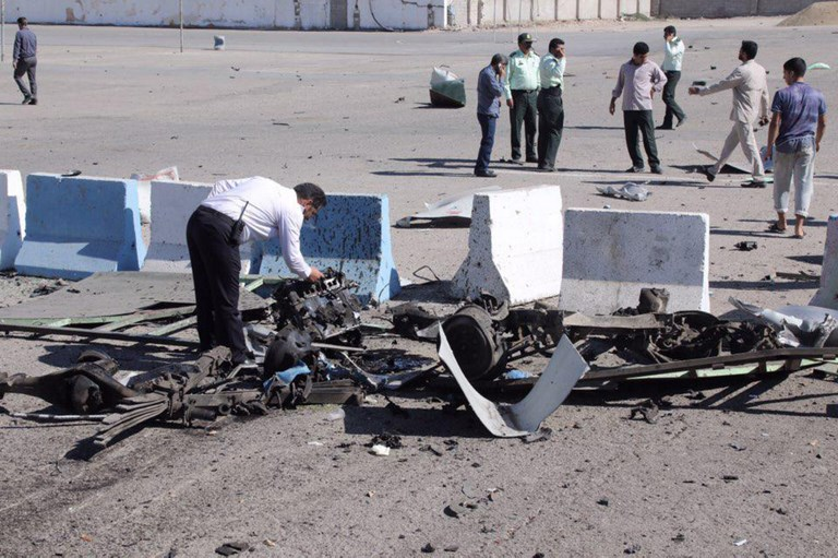 A policeman inspects the wreckage of a car bomb in the Iranian port city of Chabahar on Thursday. Photo: AFP