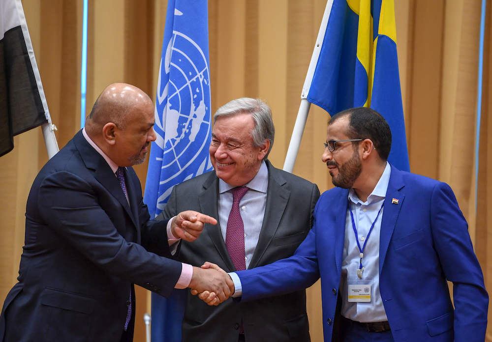 وزير الخارجية اليمني خالد اليماني (يسار) وممثل الحوثيين محمد عبد السلام يتصافحون أمام الأمين العام للأمم المتحدة أنطونيو جوتيريس في السويد في 13 ديسمبر/كانون الأول 2018. صورة: AFP