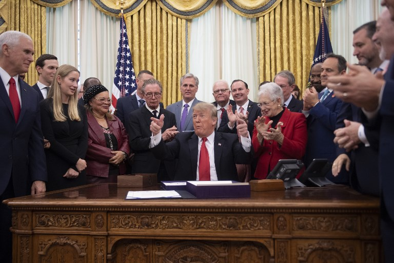 US President Donald Trump receives applause after signing bills at the White House on December 21. Photo: AFP/Jim Watson