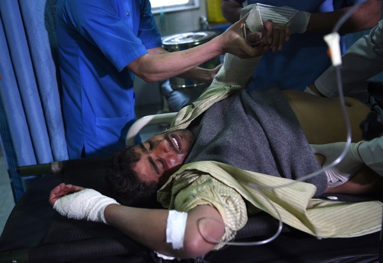 A wounded man receives medical treatment after a car bomb attack in Kabul on Monday. Photo: AFP