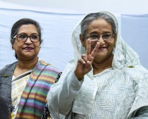 Sheikh Hasina, right,  flashes the victory symbol after casting her vote at a polling station in Dhaka. Photo: AFP