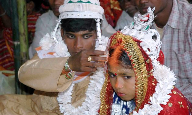 在大規模集體婚禮上,印度新郎將朱砂(印度教婚姻的神聖印記)塗在未成年新娘的額頭上。相片:AFP / Stroel